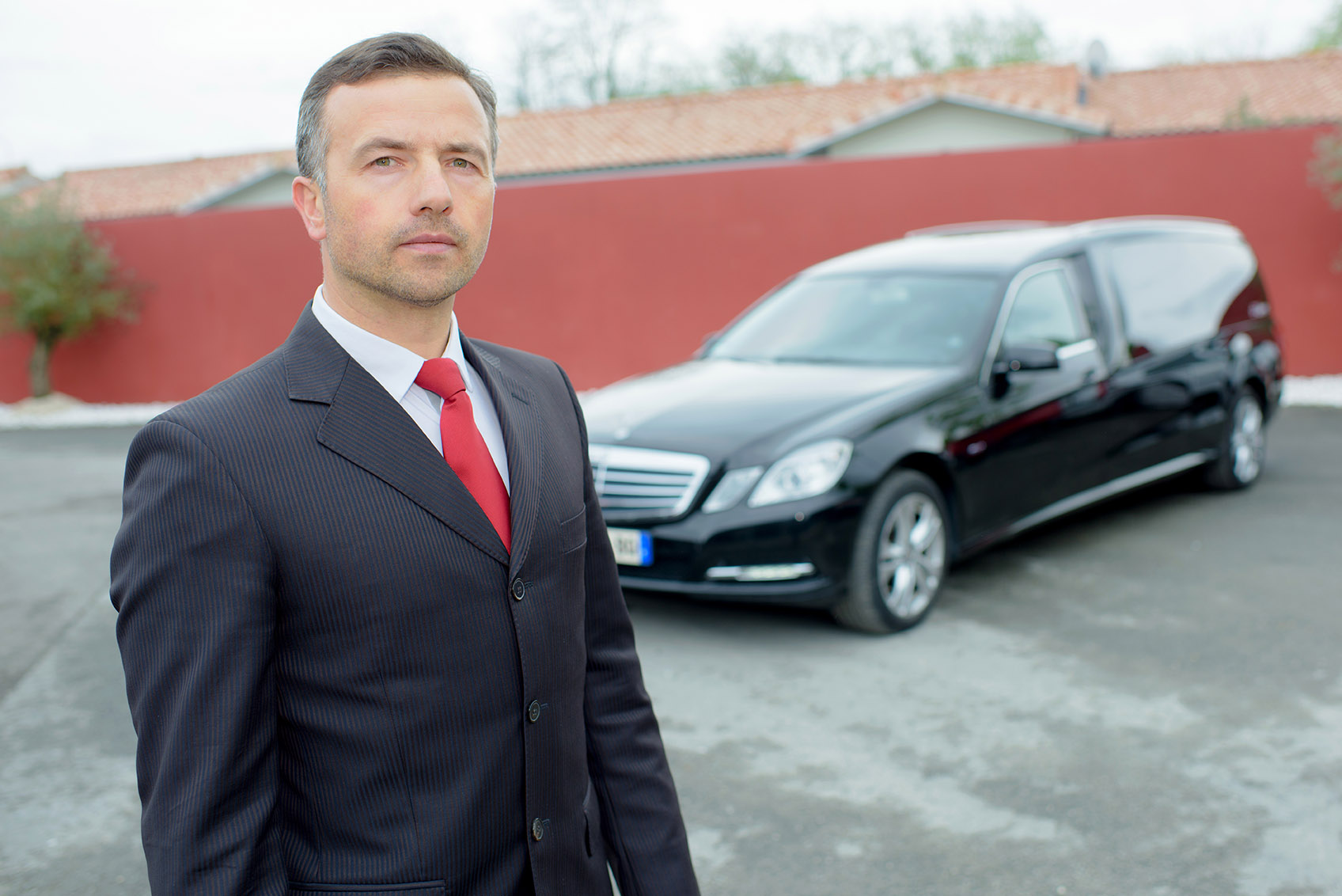 Funeral director in front of funeral cars
