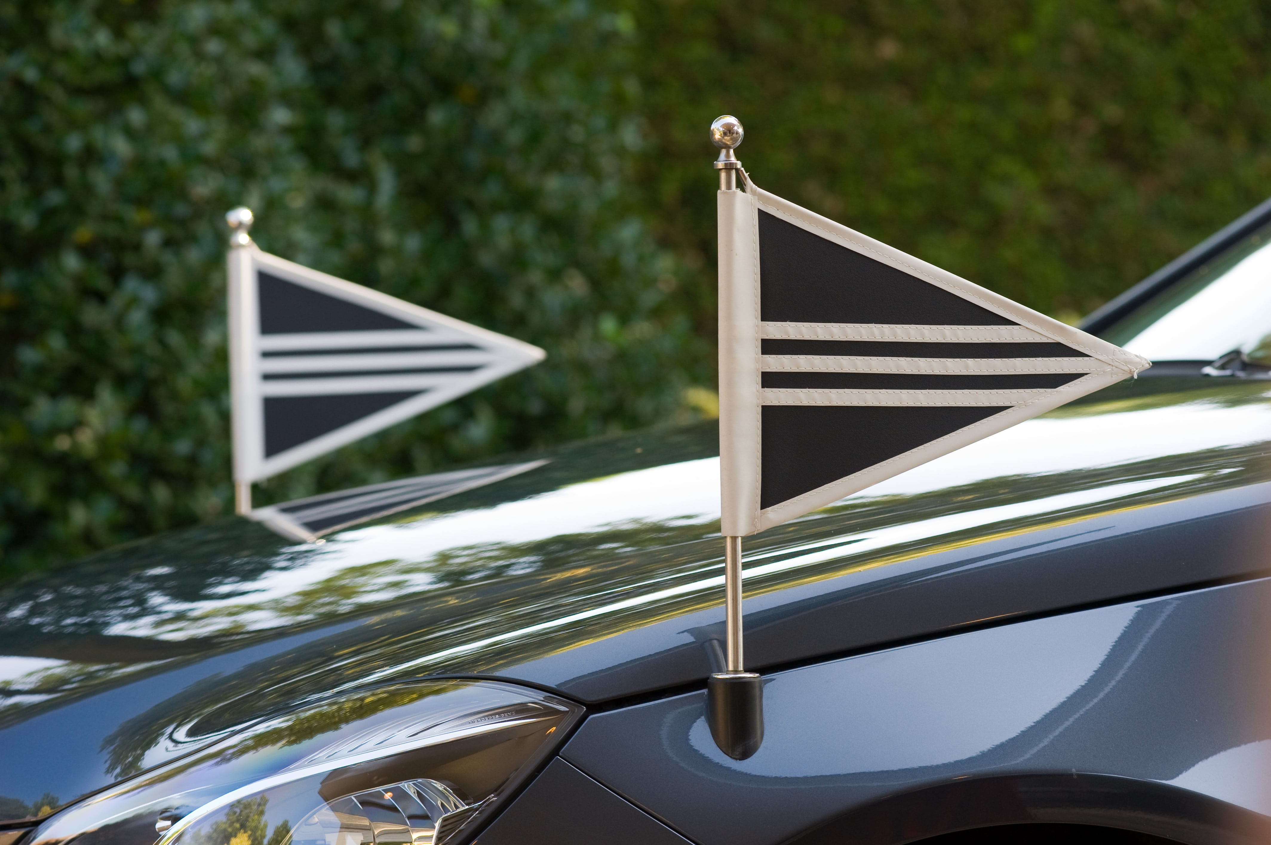 Flags on the front of a funeral car