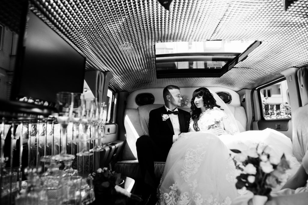 A bride and groom sit in an extravagant limo.