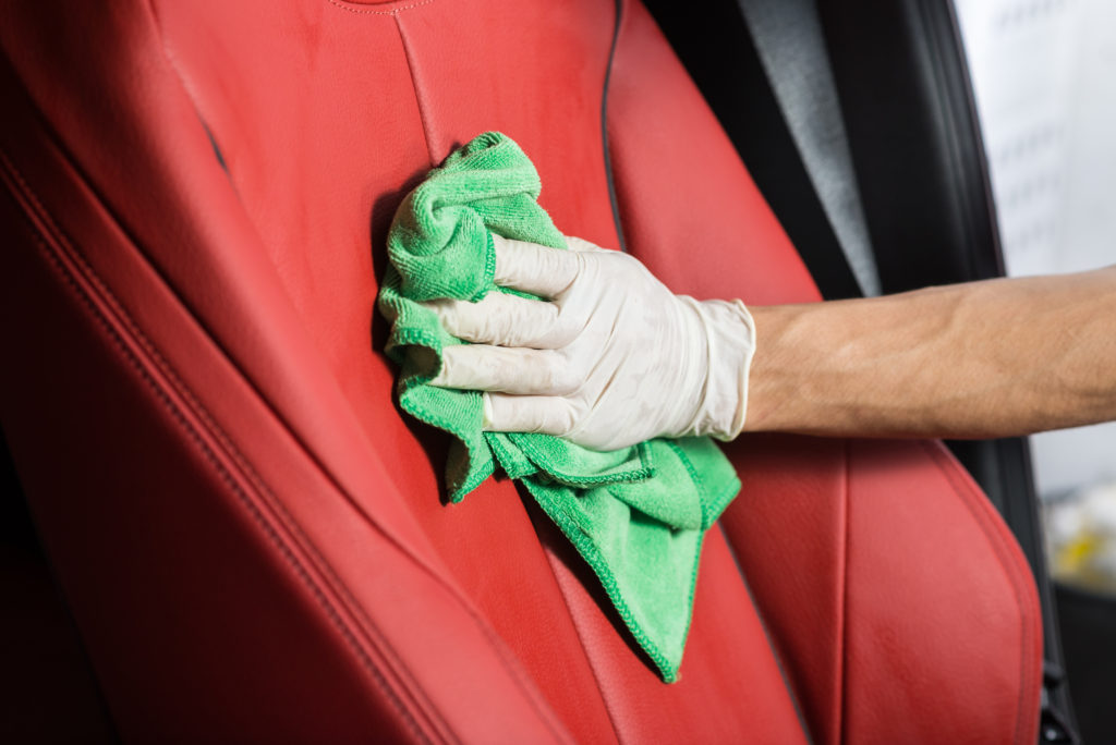 A luxury car's seat is cleaned and prepared.