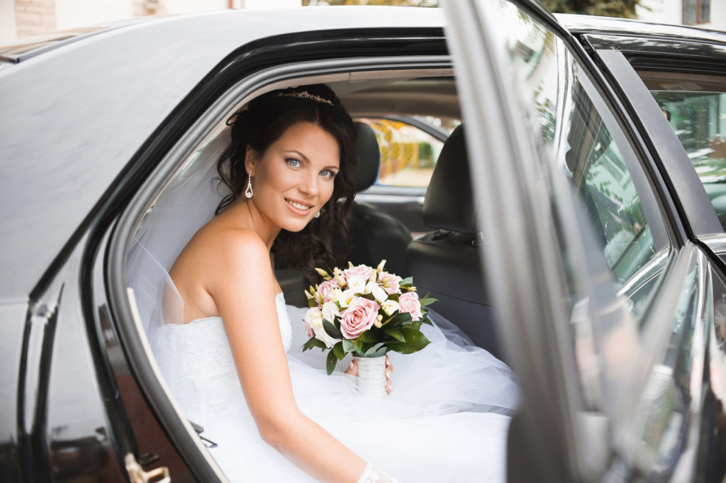 A smiling bride sits in a limousine.