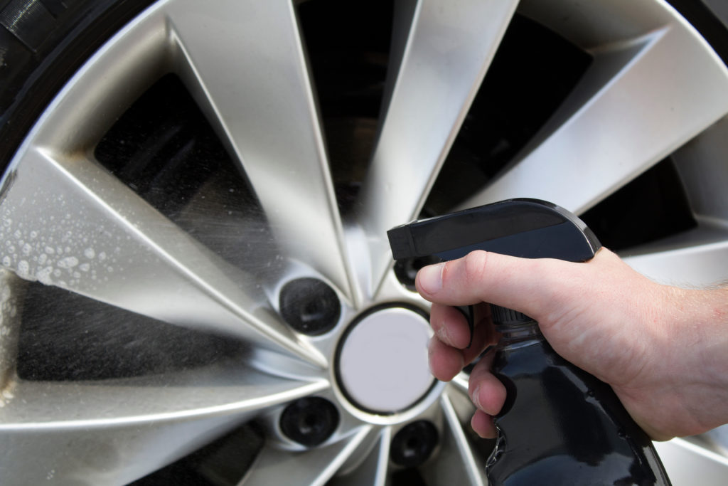 A person wearing gloves cleans a car's rim.