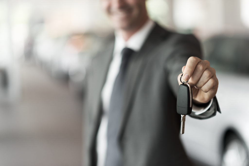 A salesperson holds out limo keys.