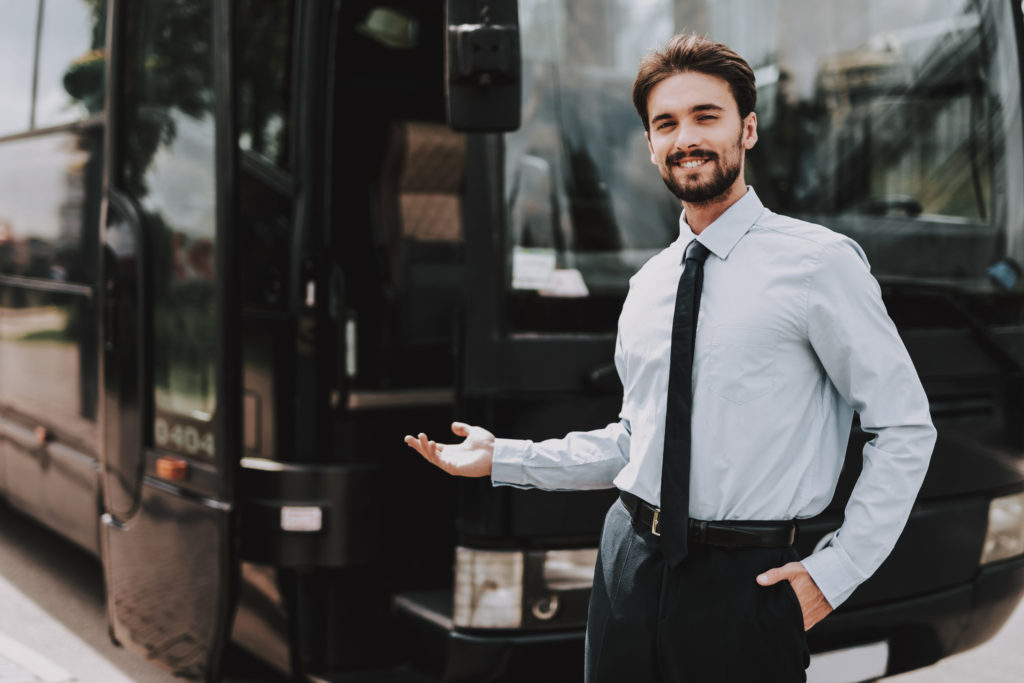 Smiling businessman standing in front of executive bus